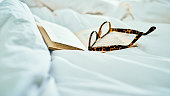 Still life shot of a book and a pair of spectacles on a bed