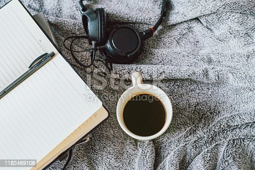 Shot of a notebook, coffee and headphones on a bed at home
