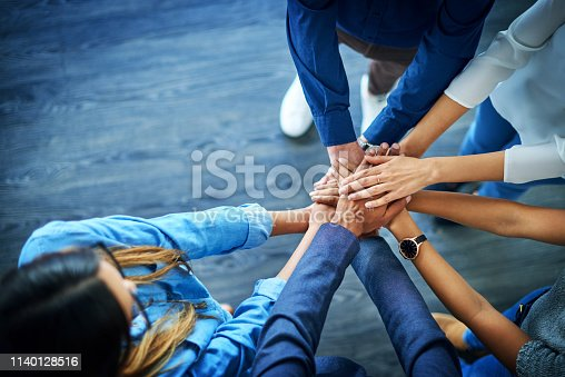 High angle shot of a group of colleagues joining their hands together in unity