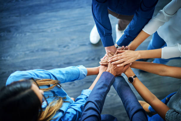 Nothing can beat united minds High angle shot of a group of colleagues joining their hands together in unity unity stock pictures, royalty-free photos & images