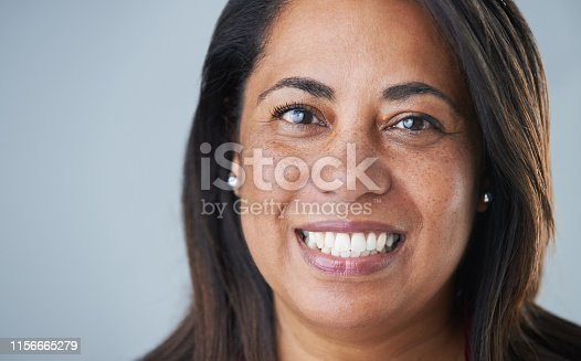 Cropped headshot of an attractive mature woman smiling at the camera while standing against a gray background in the studio