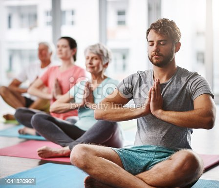 Cropped shot of a group of people meditating while practicing yoga
