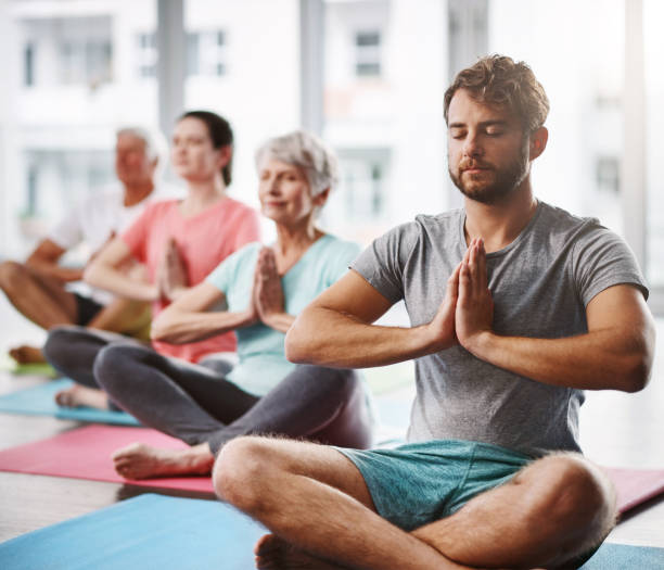 Nothing else matters Cropped shot of a group of people meditating while practicing yoga yoga class stock pictures, royalty-free photos & images