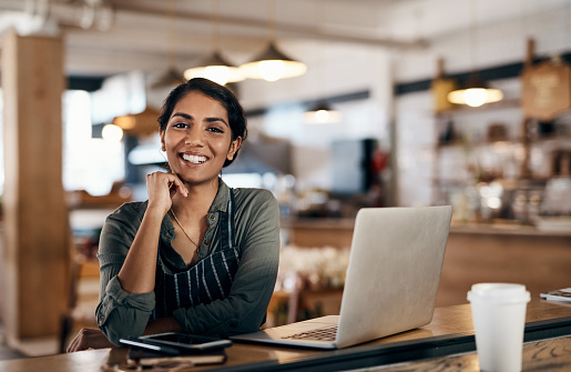 Shot of a young woman using a laptop while working in a cafe