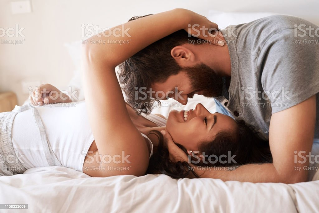Nothing enriches life like love Shot of an affectionate young couple sharing a romantic moment in the bedroom at home Adult Stock Photo