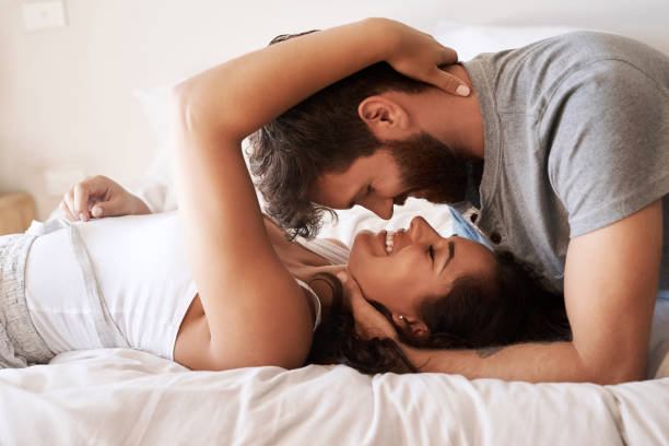 Nothing enriches life like love Shot of an affectionate young couple sharing a romantic moment in the bedroom at home amor stock pictures, royalty-free photos & images