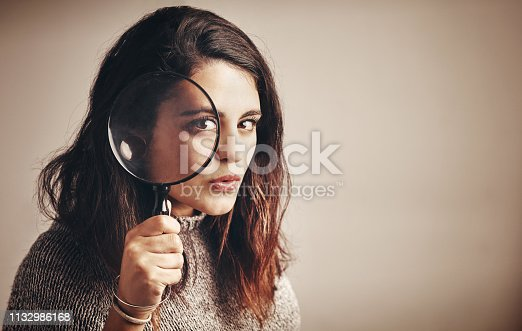 Studio portrait of a young woman looking through a magnifying glass against a brown background