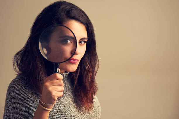 Nothing escapes my eye Studio portrait of a young woman looking through a magnifying glass against a brown background detective stock pictures, royalty-free photos & images