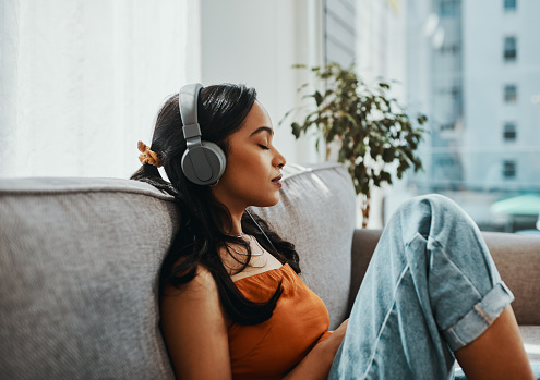 Shot of a young woman using headphones while relaxing on the sofa at home