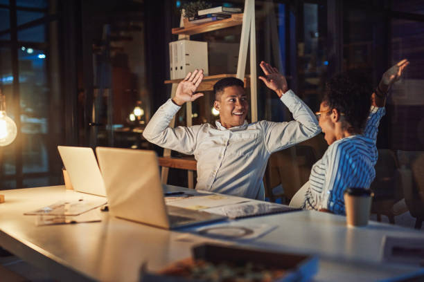 Nothing feels better than beating a deadline Shot of a young businessman and businesswoman giving each other a high five during a late night meeting passion stock pictures, royalty-free photos & images
