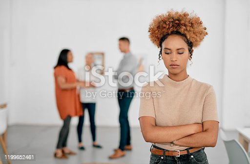Shot of a young businesswoman being excluded from her colleagues in a modern office