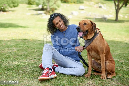 Full length shot of a handsome young man bonding and spending time with his dog outdoors at a park