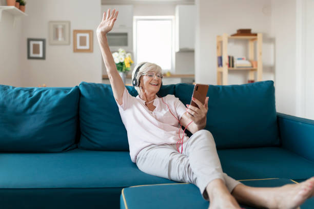 Nothing is as relaxing as listening the music Senior Woman Wearing Headphones Listens to Favorite Mp3 Digital Music on Smart Phone at Home While Sitting on Bed in the Living Room, Elderly Woman Enjoys Stereo High Quality Audio Sound from Mobile Phone on Stylish New Earphones baby boomers stock pictures, royalty-free photos & images