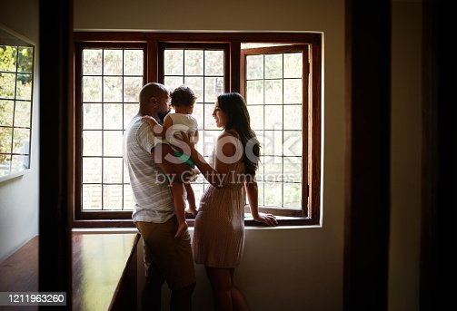 Shot of a young family looking out of the window in their new home