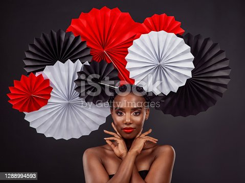 Studio shot of a beautiful young woman posing with a origami fans against a black background