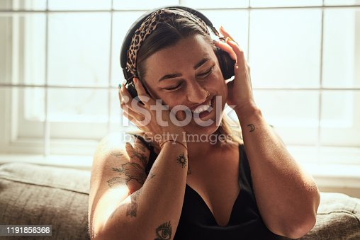 Shot of a young woman using headphones on the sofa at home