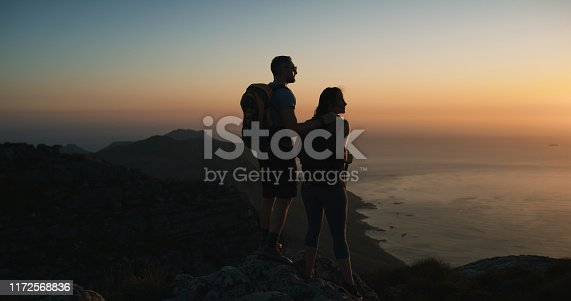 Shot of a man and woman hiking up a mountain