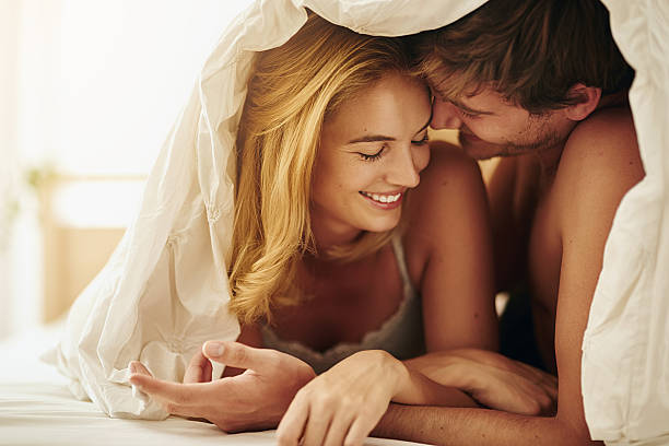 Nothing makes me feel the way you do Shot of a young couple sharing an intimate moment under the covers in bed real couples making love stock pictures, royalty-free photos & images