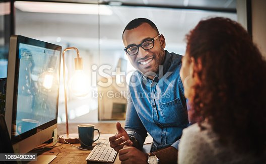 Shot of a young businessman and businesswoman having a discussion during a late night at work