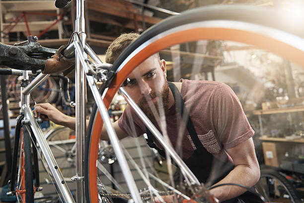Nothing replaces hard work and diligent focus Shot of a handsome young bicycle mechanic working on a customer€™'s bicycle bicycle shop stock pictures, royalty-free photos & images