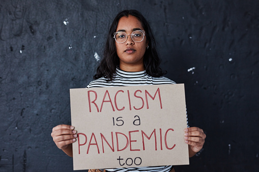 Studio shot of a young woman protesting against racism against a dark background