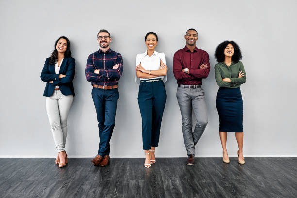 Nothing says capability like confidence Studio shot of a group of businesspeople standing in line against a grey background people in a row stock pictures, royalty-free photos & images