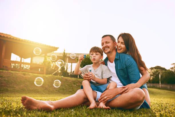 nothing says family fun like blowing bubbles - mãe criança brincar relva efeito de refração de luz imagens e fotografias de stock