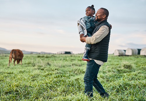 Shot of a mature man carrying his adorable daughter on a cow farm
