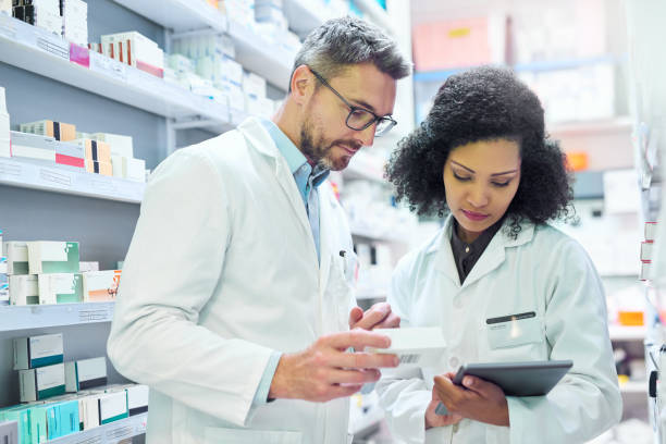 Nothing says well run pharmacy like teamwork Shot of a mature man and young woman using a digital tablet together while working in a pharmacy pharmacist stock pictures, royalty-free photos & images
