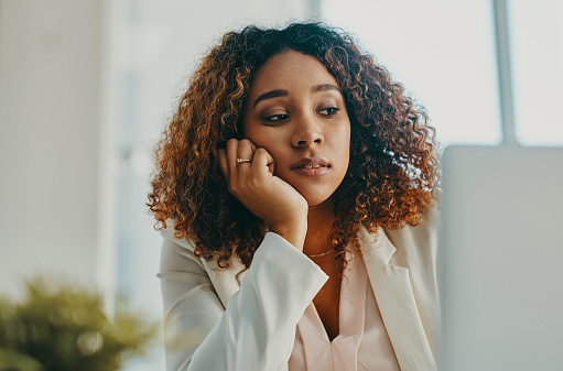 Shot of a young businesswoman looking bored while using a laptop in a modern office