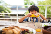Shot of an adorable little boy eating a cob of corn around a table outdoors