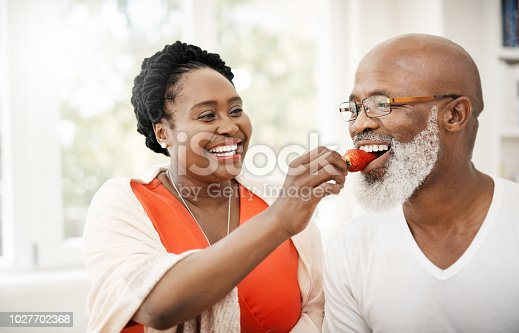Shot of a happy mature woman lovingly feeding her husband a strawberry at home