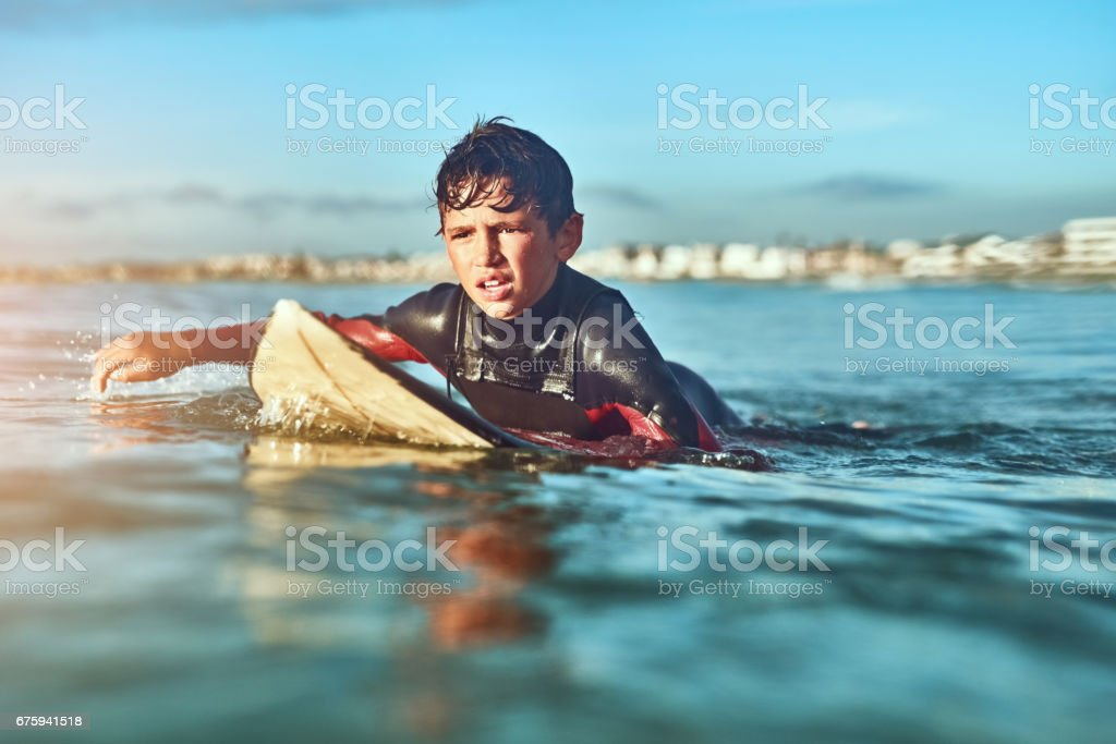Nothing will keep this grom from surfing stock photo