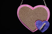 A notice board shaped like a heart on a black background