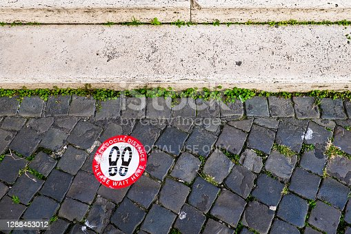 Rome, Italy, November 25 -- A adhesive notice on an ancient street paving stone indicate keep the social distance in Rome downtown at the entrance of a church, due the restrictions for the Covid-19 pandemia. Image in High Definition format.