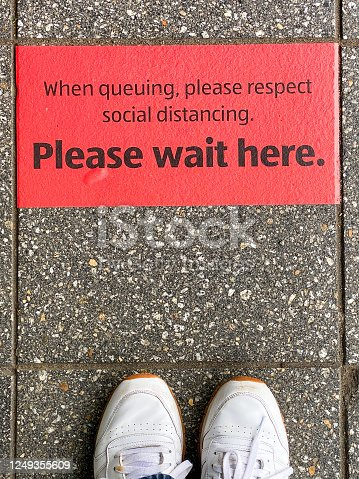 Red sticker on floor outside a supermarket with