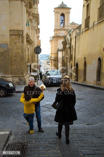 Noto, Sicily: A boy with a Barbie doll hugs his father on a street in downtown Noto, a UNESCO World Heritage site in Siracusa Province.