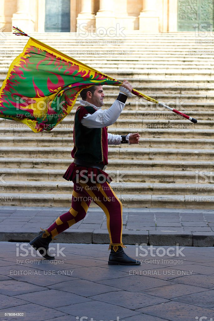 A man wearing a colorful velvet costume carries a flag in a...