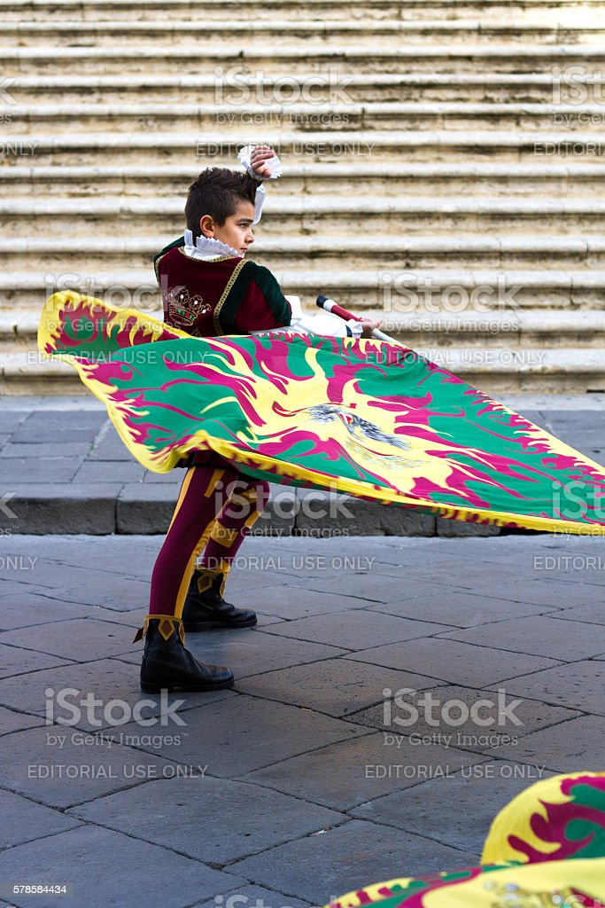 A teenage boy wearing a colorful traditional costume twirls flags in...