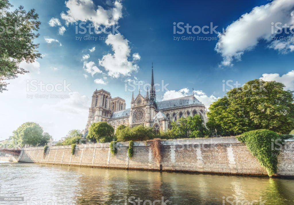 Notre Dame Cathedral in Paris, France, on a sunny day with the river Seine and dramatic clouds. stock photo