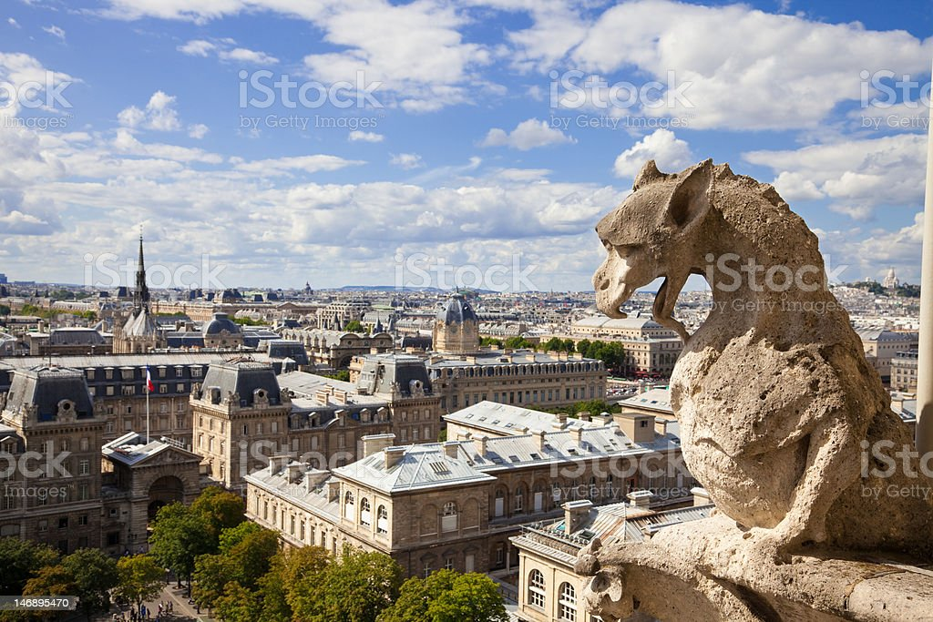 Notre Dame: Famous Chimera (dragon) overlooking the skyline of Paris royalty-free stock photo