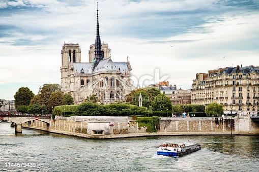 Notre-Dame de Paris Rear view pre-fire with the Seine and Bateau Mouche, showing the collapse d spire.