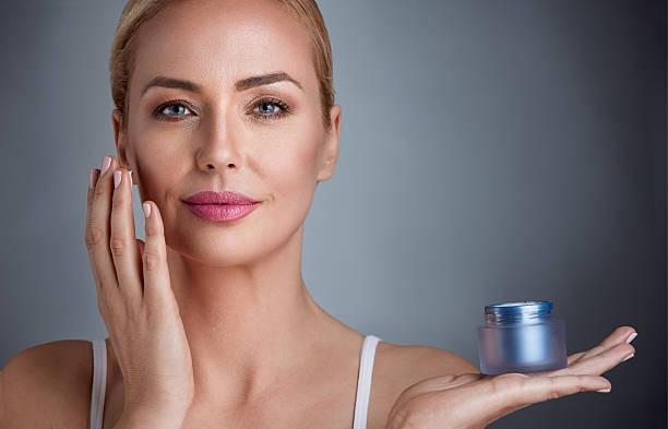nourished woman with cream - creme huid stockfoto's en -beelden