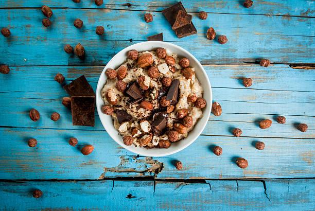 nourishing and delicious breakfast, oatmeal with hazelnuts - getreidebrei stock-fotos und bilder