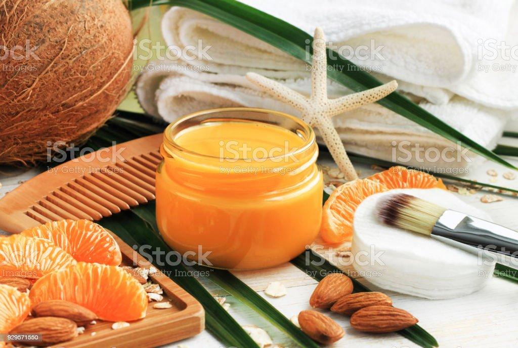 Nourishing natural skin care, bright fresh tangerine fruit slices, orange jar of aromatic facial cream, bathroom towels, stock photo