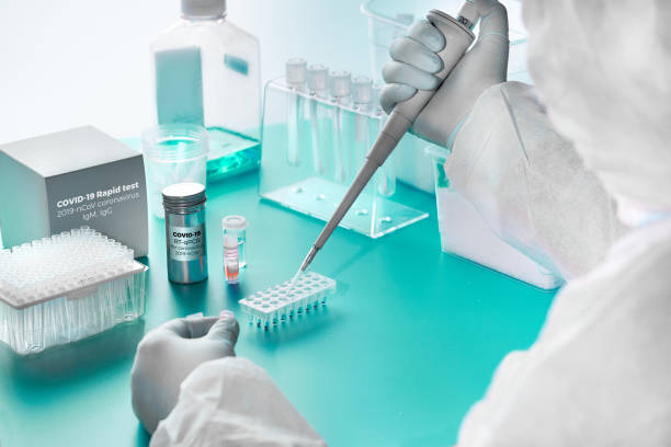 Novel coronavirus detection: pcr kit for detection of SARS-COV-2 novel coronavirus and rapid kit to detect antibodies for the virus in blood of recovered patients. Epidemiologist works in test lab. stock photo