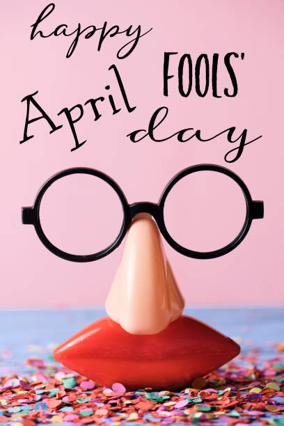 novelty glasses and text happy april fools day a pair of fake eyeglasses, with nose and mouth, and the text happy april fools day, on a rustic surface full of confetti, against a pink background april fools day stock pictures, royalty-free photos & images