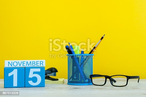 868951648 istock photo November 15th. Day 15 of month, wooden color calendar on yellow background with office supplies. Autumn time 867513326