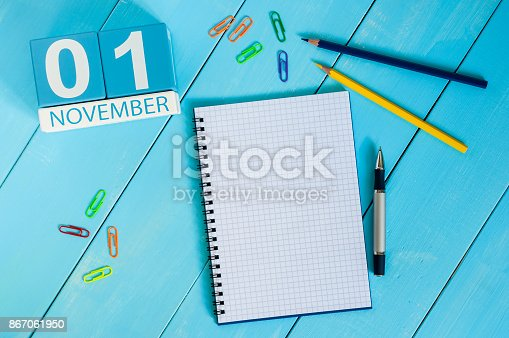 868951648 istock photo November 1st. Day 1 of month, wooden color calendar on blue background. Autumn time. Empty space for text 867061950