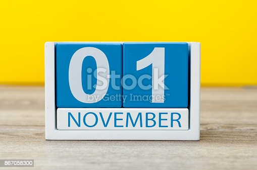 868951648 istock photo November 1st. Day 1 of month, wooden color calendar on yellow background. Autumn time 867058300